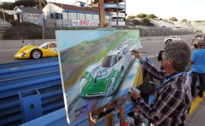 "Official artist Bill Patterson paints while cars race past during the Porsche Rennsport Reunion V at Laguna Seca Raceway near Salinas, California, September 26, 2015. The three-day reunion is billed by organizers as ""the world's largest gathering of Porsche racecars, renowned drivers, and Porsche collector cars.""  REUTERS/Michael Fiala"